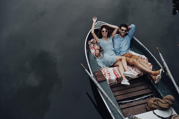 Speels voelen. bovenaanzicht van mooie jonge paar omarmen en glimlachen terwijl liggend in de boot