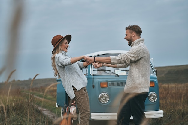 Speels voelen. mooie jonge paar hand in hand en glimlachen terwijl ze in de buurt van de blauwe retro-stijl minibusje staan