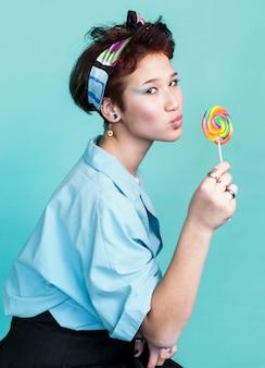Speels vrouwelijk model poseren met lolly