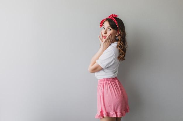 Speels wit meisje met rood lint dat pret heeft. positief krullend vrouwelijk model dat over schouder kijkt met verbaasde gezichtsuitdrukking.