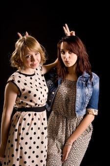 Speelse aantrekkelijke jonge meisjes die naast elkaar staan en vsigns achter elkaars hoofden maken