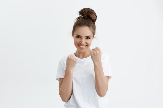 Speelse aantrekkelijke moderne vrouw die breed lacht terwijl ze vuisten opheft alsof ze bokst of verdedigt