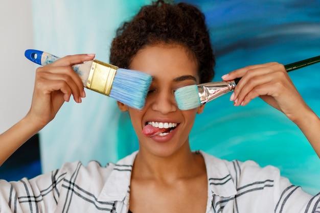 Speelse afrikaanse vrouwelijke kunstenaar die borstels houdt en grimassen maakt, die tong toont.