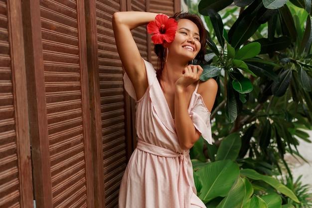 Speelse aziatische vrouw met hibiscus bloem in haren en in roze jurk poseren in luxe tropische resort.