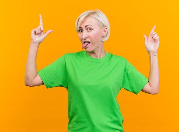 Speelse blonde slavische vrouw die van middelbare leeftijd camera bekijkt die tong benadrukt die omhoog wijst geïsoleerd op gele achtergrond