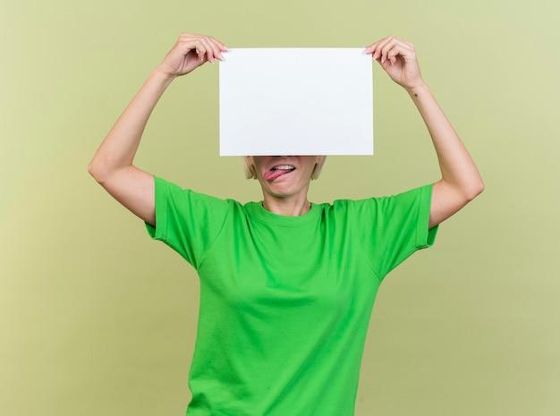 Speelse blonde slavische vrouw op middelbare leeftijd die blanco papier voor ogen houdt die tong tonen die op olijfgroene muur wordt geïsoleerd