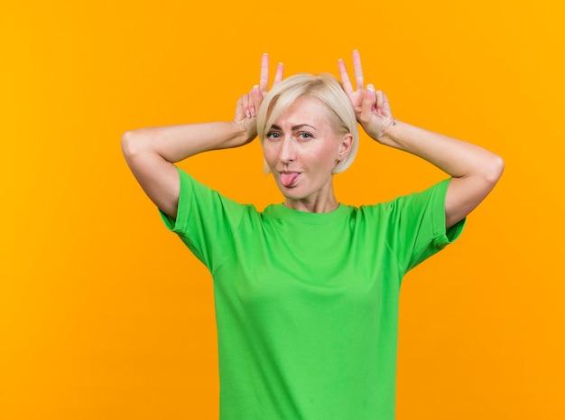 Speelse blonde slavische vrouw op middelbare leeftijd die camera bekijkt die tong toont die konijntjesoren maakt die op gele achtergrond worden geïsoleerd