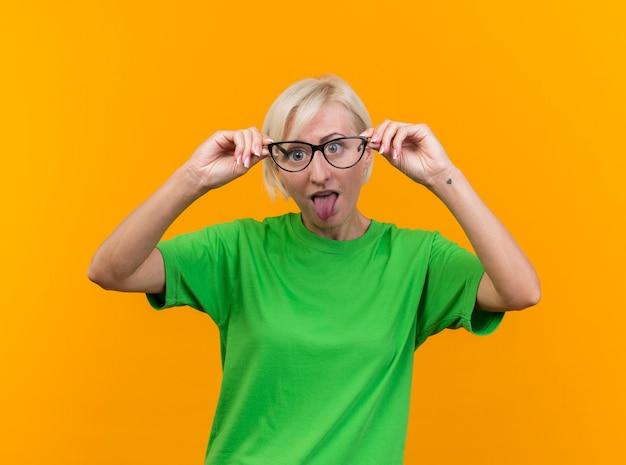 Speelse blonde slavische vrouw op middelbare leeftijd die de bril van de cameraholding voor ogen bekijken die tong tonen die op gele achtergrond wordt geïsoleerd