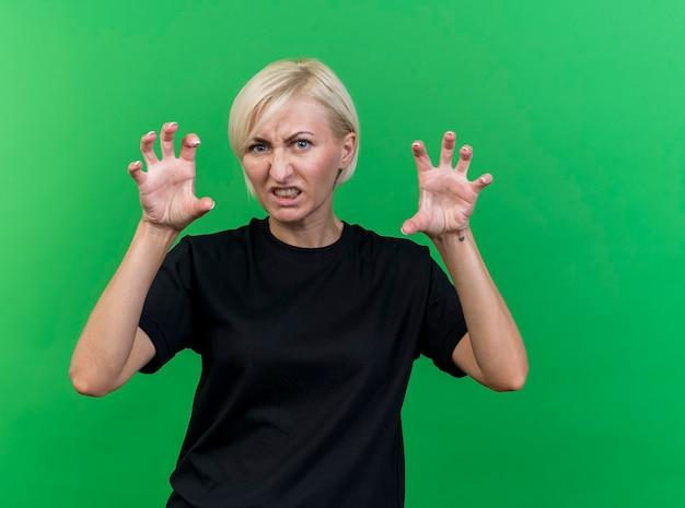 Speelse blonde slavische vrouw van middelbare leeftijd kijken camera doet tijger brullen en poten gebaar geïsoleerd op groene achtergrond met kopie ruimte