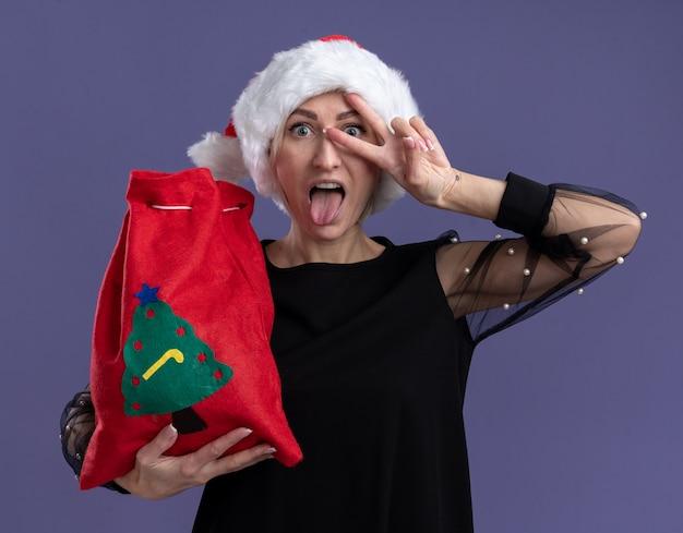 Speelse blonde vrouw van middelbare leeftijd met kerstmuts bedrijf kerstzak kijken camera weergegeven: tong en v-teken symbool in de buurt van oog geïsoleerd op paarse achtergrond