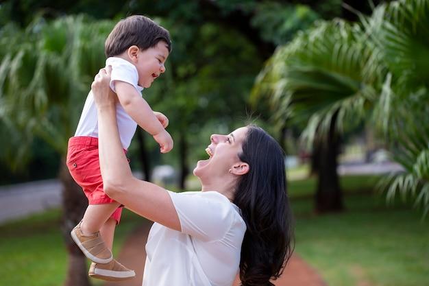 Speelse braziliaanse jonge moeder die babyjongen op achtergrond bij park opheft