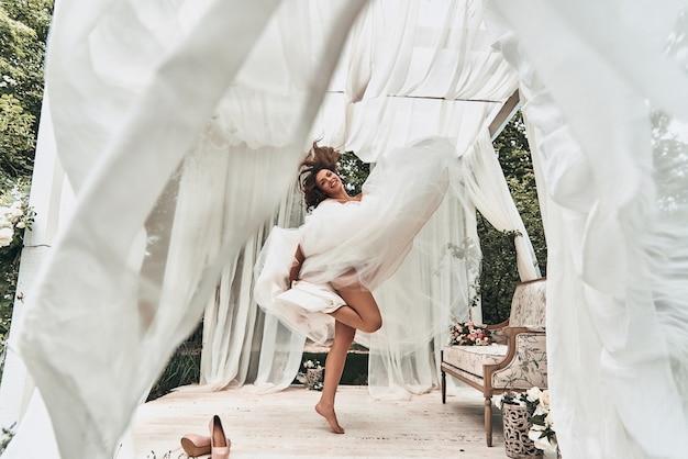 Speelse bruid. volledige lengte van aantrekkelijke jonge vrouw in trouwjurk die lacht terwijl ze danst in het huwelijkspaviljoen buitenshuis