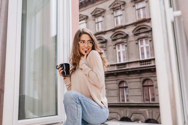 Speelse bruinharige vrouwenzitting dichtbij groot raam met geïnspireerde glimlach
