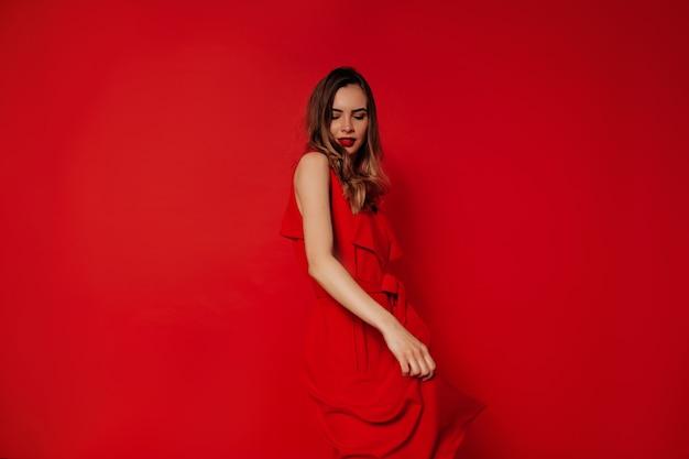 Speelse charmante dame draagt rode jurk dansen en plezier maken