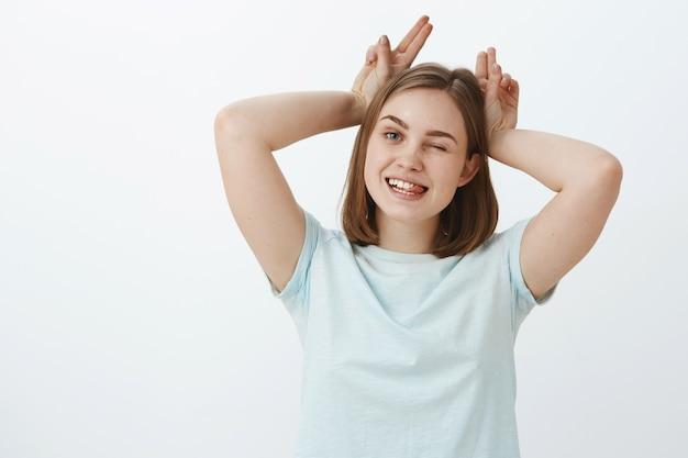 Speelse en grappige, zorgeloze jonge vrouw die geniet van het leven tijd doorbrengen met jongere zus spelen met koe of dier met hoorns knipogen vrolijk tong uitsteken en vingers op hoofd houden