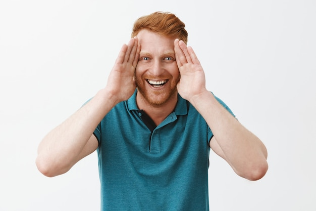 Speelse en vrolijke knappe jonge roodharige man met borstelharen die de handpalmen langs het gezicht houdt en breed lacht, kiekeboe speelt