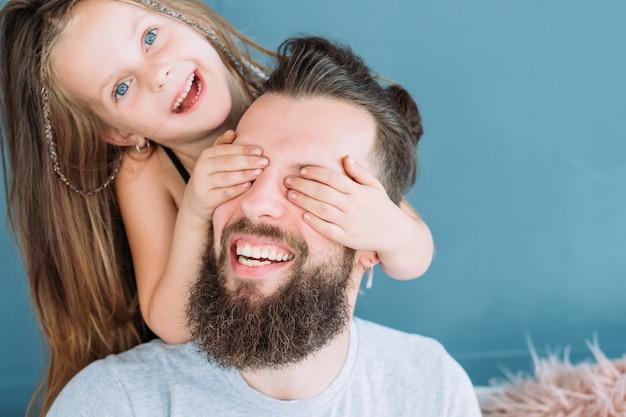 Speelse gezinsvakantie. dochter liefde expressie. klein meisje dat papa's ogen van achteren bedekt