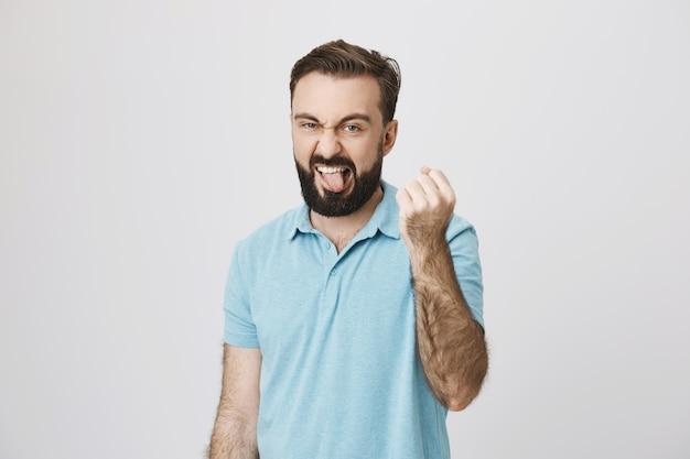 Speelse grappige man die tong toont en vuist schudt, ik zal je gebaar laten zien