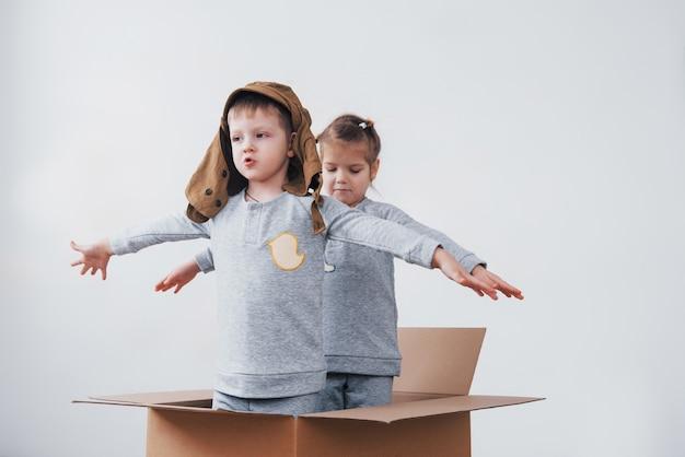 Speelse jeugd. kleine jongen plezier met kartonnen doos. jongen die zich voordoet als piloot. kleine jongen en meisje plezier thuis