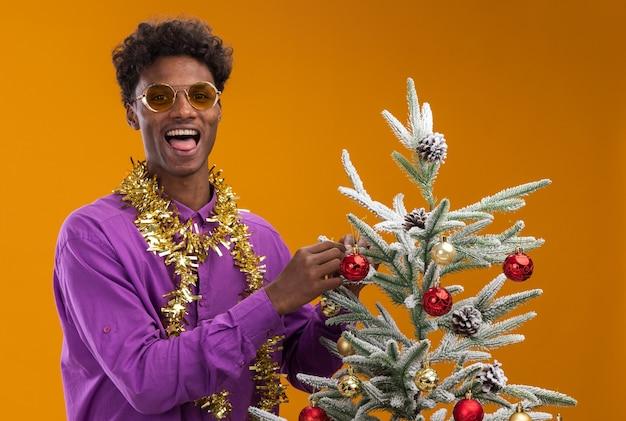 Speelse jonge afro-amerikaanse man met bril met klatergoud slinger rond de nek staande in de buurt van de kerstboom en versiert het met kerstballen