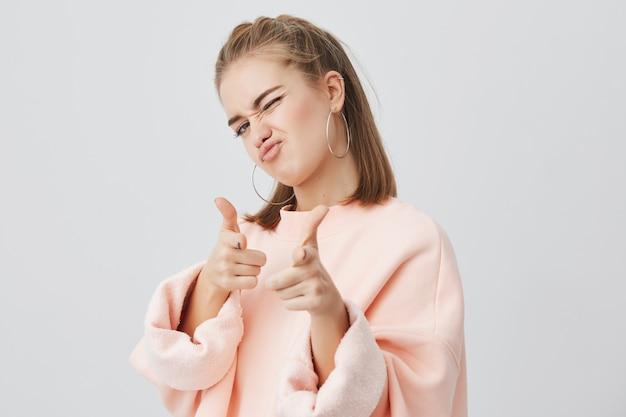 Speelse jonge blanke vrouw met recht blond haar in roze sweatshirt met lange mouwen, staand, spottend, wijzend met haar wijsvingers naar jou
