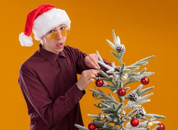 Speelse jonge blonde man met kerstmuts en bril staan in profiel te bekijken in de buurt van versierde kerstboom op oranje achtergrond