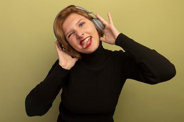 Speelse jonge blonde vrouw die een koptelefoon draagt en aanraakt die naar de voorkant kijkt en tong toont en knipoogt geïsoleerd op olijfgroene muur
