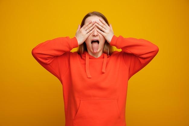 Speelse jonge blonde vrouw die ogen behandelt met handen die tong tonen