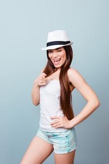Speelse jonge coquette wijst op de camera, ze is op vakantie, flirten, zomer lichte outfit, hoed, dragen op blauwe ruimte