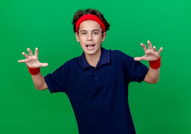 Speelse jonge knappe sportieve jongen dragen hoofdband en polsbandjes met beugels kijken camera doen tijger brullen en poten gebaar geïsoleerd op groene achtergrond