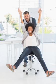 Speelse jonge man duwende vrouw op stoel in office