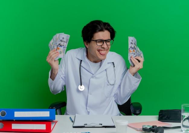 Speelse jonge mannelijke arts die medische mantel en stethoscoop met bril draagt die aan bureau met medische hulpmiddelen zit die geld toont die tong met gesloten ogen toont die op groene muur wordt geïsoleerd