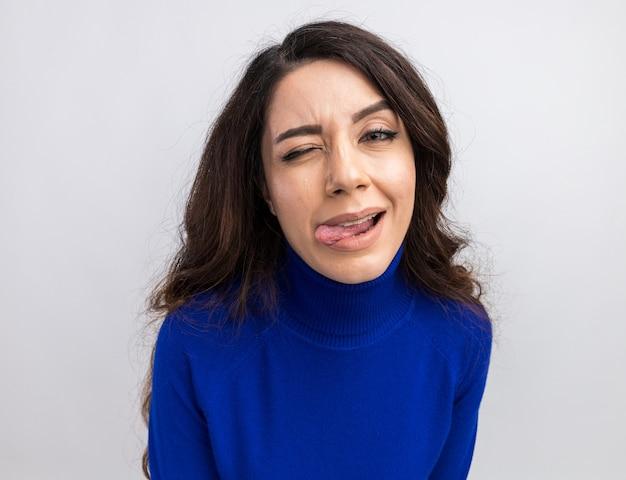 Speelse jonge mooie vrouw die naar de voorkant kijkt die knipoogt en tong toont die op een witte muur wordt geïsoleerd