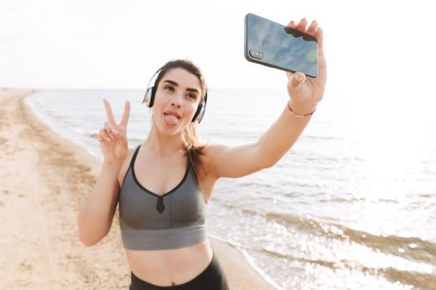 Speelse jonge sportvrouw die zich bij het strand bevindt