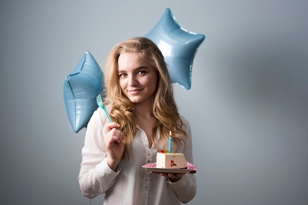 Speelse jonge vrouw die verjaardagscake eet
