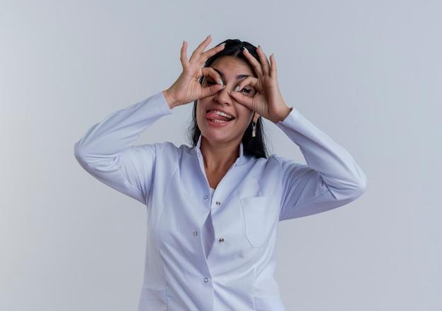 Speelse jonge vrouwelijke arts die medische mantel draagt die tong toont die blikgebaar geïsoleerd kijkt