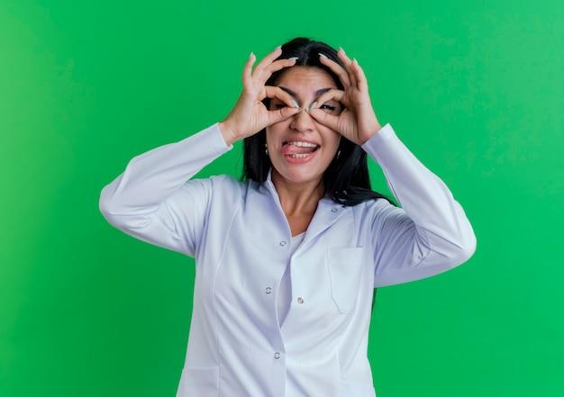 Speelse jonge vrouwelijke arts die medische mantel draagt die toont tong doet blikgebaar met handen als verrekijker