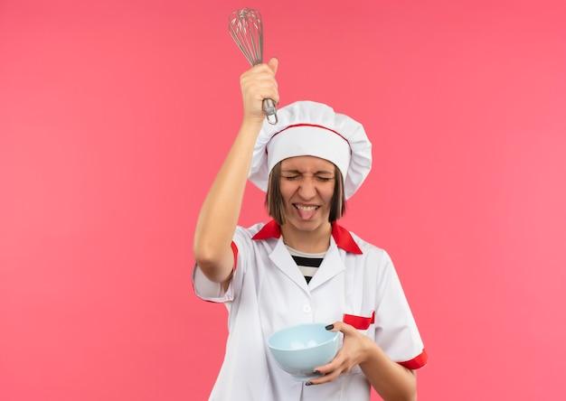 Speelse jonge vrouwelijke kok in chef-kok uniforme kom houden en verhogen klop boven het hoofd en tonen tong met gesloten ogen geïsoleerd op roze achtergrond met kopie ruimte