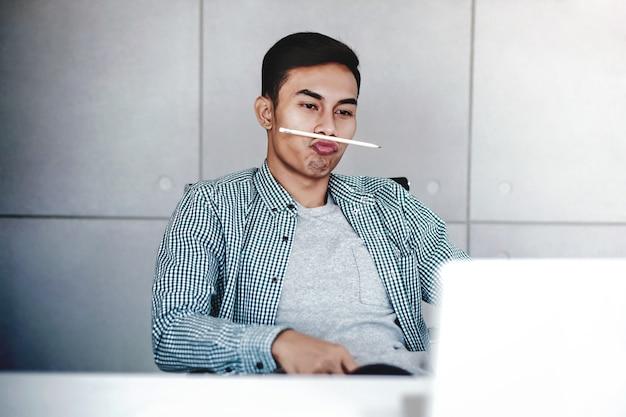 Speelse jonge zakenman die aan computerlaptop in bureau werkt