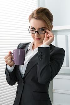 Speelse jonge zakenvrouw haar bril opstijgen en kijken. vrouw stond bij het raam met een kopje thee tijdens koffiepauze