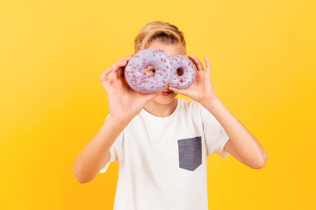Speelse jongen die donuts houdt