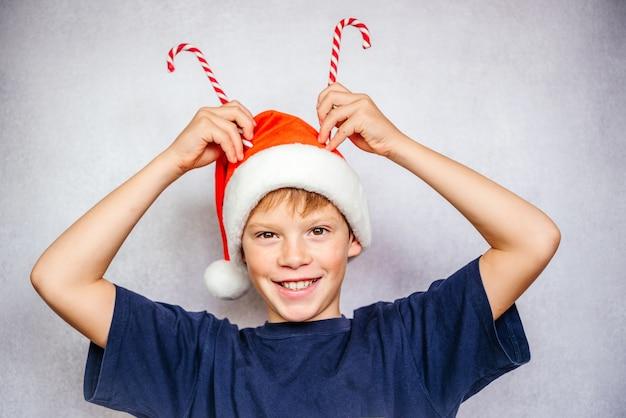 Speelse jongen met kerstmuts die zuurstokken op zijn hoofd zet om rendiergeweien te maken
