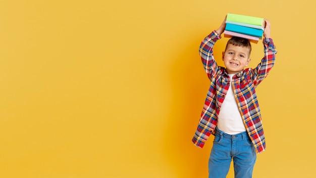 Speelse jongen met stapel boeken op zijn hoofd
