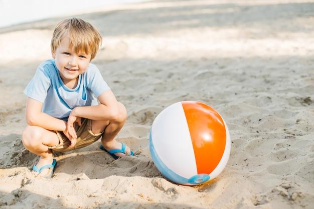 Speelse jongen zit naast wind bal