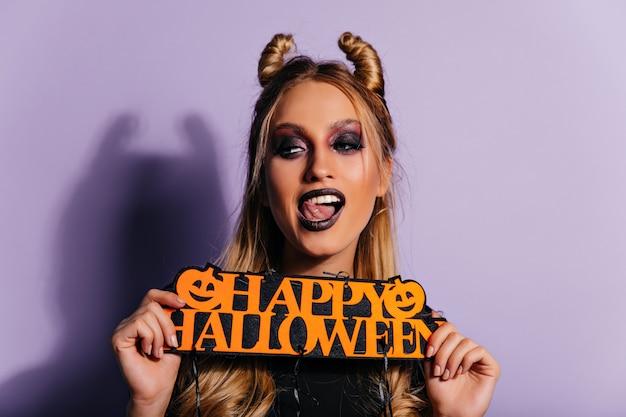 Speelse kaukasische jonge vrouw die van halloween-fotoshoot geniet. blond meisje in vampierkleding poseren met feest decor.