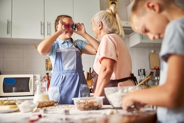 Speelse kleindochter knoeit met koekjesvormpjes tijdens het koken met het gezin