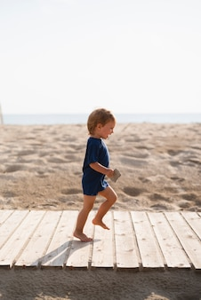 Speelse kleine jongen draait op strand