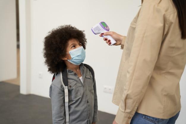 Speelse kleine schooljongen met gezichtsmasker die wacht terwijl zijn leraar de temperatuur meet