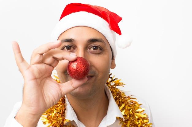 Speelse man die neus bedekt met kerstbal