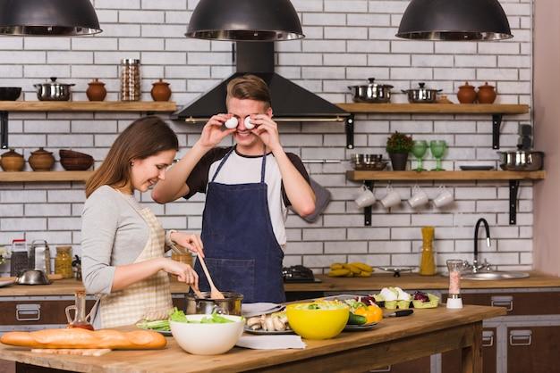 Speelse man die ogen behandelt met eieren terwijl vrouw het koken